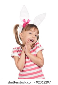 Portrait of surprised little girl with bunny ears over white background