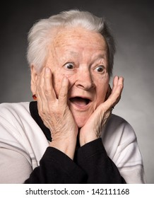 Portrait of surprised old woman on a gray background