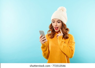 Portrait of a surprised pretty girl dressed in winter clothes looking at mobile phone isolated over blue background