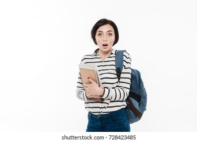 Portrait of a surprised pretty teenage girl with backpack holding books while standing and looking at camera isolated over white background
