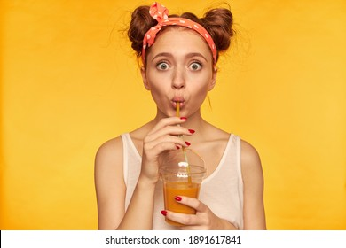 Portrait of surprised, red hair girl with red doted hairband. Shocked with taste, make a sip. Wearing white shirt and holding her smoothie. Watching at the camera isolated over yellow background