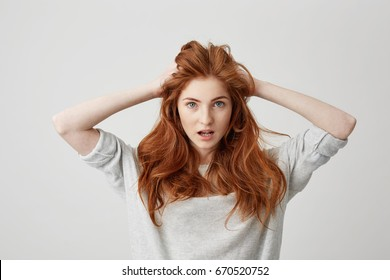 Portrait of surprised redhead beautiful girl looking at camera with opened mouth touching head over white background.