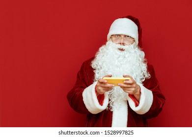 Portrait of surprised santa stands on red background with smartphone in hands, looks into camera with shocked face. Santa gamer isolated on red background. Xmas concept