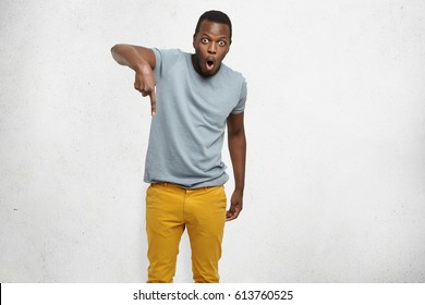 Portrait of surprised and shocked stylish young black customer having astonished look pointing index finger down, showing drop in prices. Fascinated dark-skinned man gesturing while posing at studio