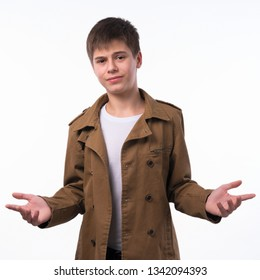 Portrait of surprised teen boy with divorced raised hands isolated on white background. A boy with a surprised face looks straight into the camera.