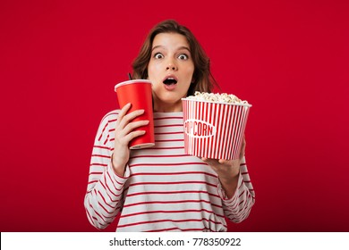 Portrait of a surprised woman holding popcorn and plastic cup isolated over pink background