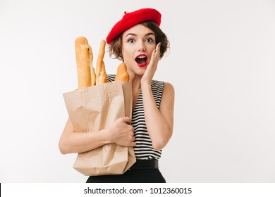 Portrait of a surprised woman wearing beret holding paper bag with long loaf isolated over white background