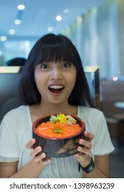 Portrait of surprised young asian woman holding japanese food dish in restaurant