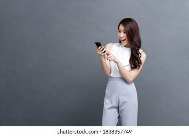 Portrait von überraschten jungen Asiaten, die Mobiltelefon auf einzeln auf grauem Hintergrund verwenden
