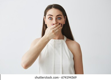 Portrait of surprised young brunette girl covering mouth with hand looking at camera over white background.