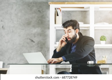 Portrait of surprised young businessman talking on the phone and using laptop in modern office. Stress concept