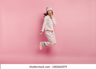 Portrait of surprised young lady wears casual pyjamas, eyemask and warm home boots, jumps in air, shocked to oversleep in morning, isolated over pink background. People and bed time concept.