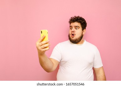 Portrait of surprised young overweight man on pink background looks into smartphone screen with shocked face wearing white t-shirt. Emotional fat guy doing selfie, isolated.