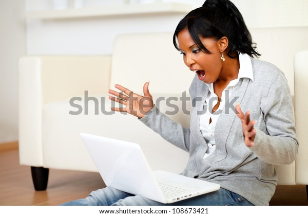Portrait of a surprised young woman browsing the Internet at home with her laptop while is sitting on the floor