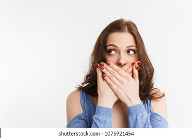 Portrait of a surprised young woman covering mouth with hands isolated over white background