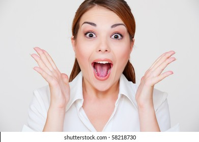 portrait of surprised young woman over grey background