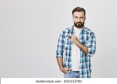 Portrait of suspicious bearded man pointing left with one hand and looking at camera, standing over gray background. Guy who went on date with girl from social network not sure it was her true photos
