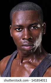 Portrait of sweaty handsome young athletic man with bold expression of confidence on black background