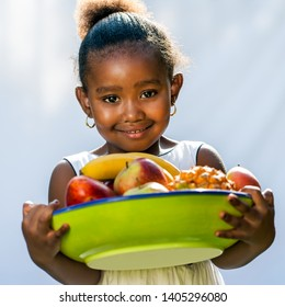 Portrait of sweet Afro American girl with fruit bowl.Isolated against light background