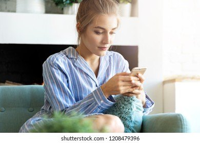 Portrait of sweet caucasian model texting on trendy smartphone. Pretty girl sitting in pyjamas at home with nice interior. Technology and morning concept. Blurred background