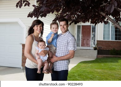 Portrait of sweet family standing in front of their house