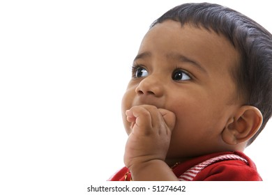 Portrait of sweet indian baby in red clothes looking left.