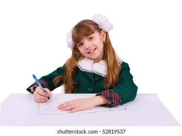 Portrait of a sweet little girl at her classroom, writing an exam. A happy schoolgirl doing her homework. Young student writing.