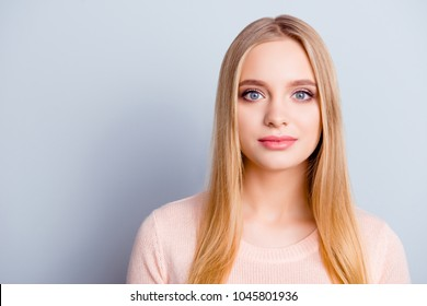 Portrait of sweet lovely tender gentle innocent peaceful girl with long smooth straight natural blonde hairdo haircut  big blue eyes dressed in beige winter warm pullover isolated on gray background