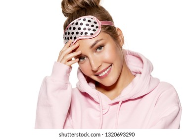 Portrait of sweet model in comfortable pyjamas and sleeping mask. Bedtime routine concept. Pretty young woman happily smiling and posing in studio on white background