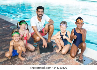 Portrait of swimming instructor with children at poolside