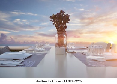 Portrait of a table of a restaurant near the sea with the sunset in the background.Concept: summer, freedom, restaurant