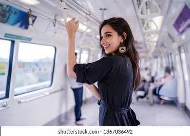 Portrait of a tall, slim, elegant, attractive, slim and beautiful Indian Asian woman taking the train alone. She is smiling as she holds onto the handrails.