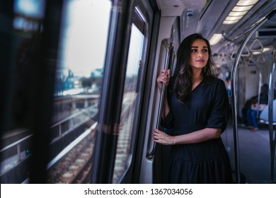 Portrait of a tall, slim, elegant and beautiful Indian Asian woman taking the train alone. She is leaning near the window and watching the scenery go by. The train is modern and clean.