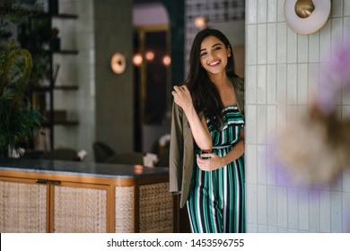 Portrait of a tall, slim, elegant and beautiful Indian Asian woman in an elegant jumper with a green jacket draped over her shoulders. She is smiling as she stands in a well-appointed home or room.