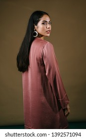 Portrait of a tall, slim and elegant Malay Asian Muslim woman in a salmon pink silk traditional dress (baju kurung) in a studio. She is looking over her shoulder and we see her long, lustrous hair.