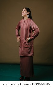 Portrait of a tall, slim and elegant Muslim woman in a salmon pink silk traditional dress (baju kurung) in a studio. She is smiling and looks confident as she has her hands on her hips.
