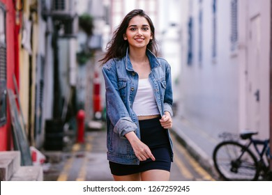 Portrait of a tall, young and elegant Indian Asian woman walking down an alley in the city during the day. She is wearing a retro denim jacket over a blue dress and white top and smiling confidently.