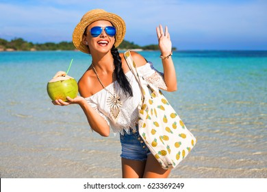 Portrait of a  tanned  young cute happy girl on the beach, ocean. Dressed in denim shorts, top, straw hat, sunglasses, a bag with pineapple, drinking coconut, laughing, relaxing on a tropical island