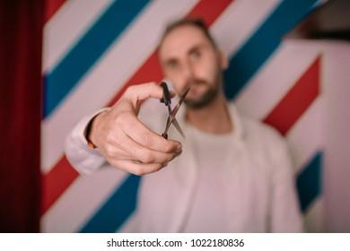 Portrait of tattooed male barber holds sharp scissors