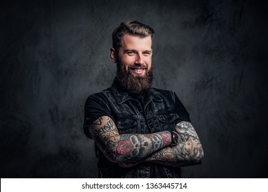 Portrait of a tattooed man with beard and hairstyle posing with his arms crossed, smiling and looking at a camera. Studio photo against a dark wall