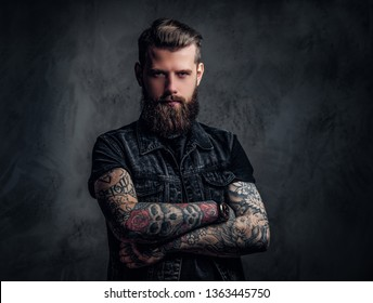 Portrait of a tattooed man with beard and hairstyle posing with his arms crossed. Studio photo against a dark wall