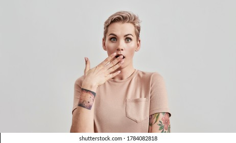 Portrait of a tattooed woman with pierced nose and short hair in beige t shirt looking surprised at camera with hand over her mouth isolated over light background. Front view. Web Banner
