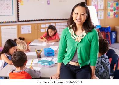 Portrait of teacher in classroom with elementary school kids