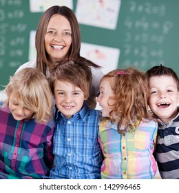Portrait of teacher in classroom with his laughing students in the classroom