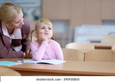 Portrait of a teacher explaining something to a smiling schoolgirl in a classroom. Special place for your next. little girl is distracted