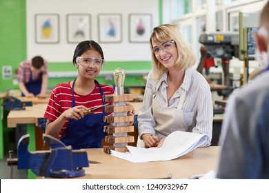 Portrait Of Teacher Helping Female High School Student Building Lamp In Woodwork Lesson