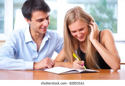 Portrait of teacher helping young student with her studies in college or school classroom after lesson