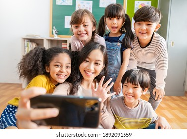 Portrait of teacher and student using smartphone selfie say hi at elementary school. The group of happy fun children making selfie in classroom.
