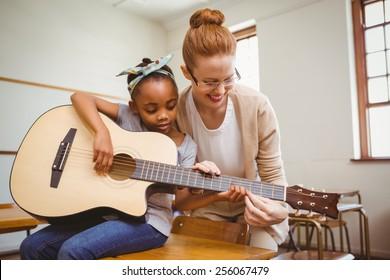 Portrait of teacher teaching cute little girl to play guitar in classroom