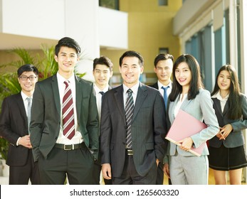 portrait of a team of asian business people standing in company lobby